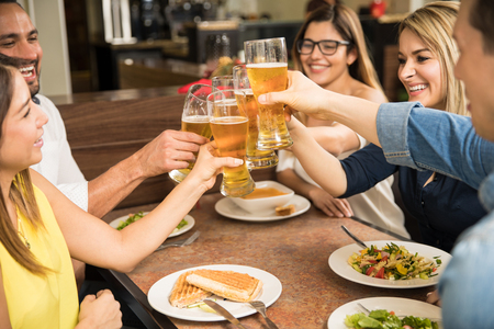 Closeup of a group of young adults drinking beer and making a toast in a restaurant