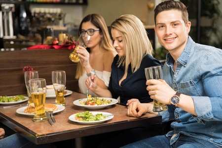 Group of young adults drinking beer at a restaurant and having a good time