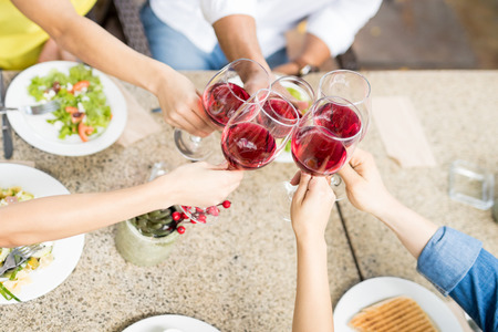 Top view of a group of five friends making a toast with wine while eating dinner together