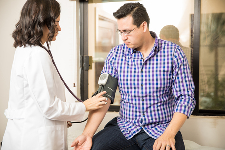 physical exam: Young female doctor using a sphygmomanometer to measure a patients blood pressure Stock Photo