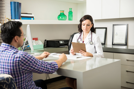 a lady doctor: Attractive young female doctor looking at a patients history during a consultation in her office Stock Photo