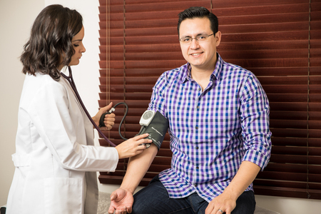 cuff: Portrait of a handsome young Hispanic patient getting his blood pressure checked by a doctor and smiling Stock Photo