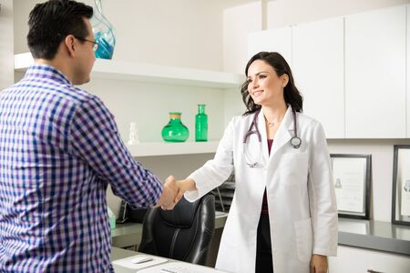 Portrait of a beautiful female doctor greeting a patient into her office with a handshake Reklamní fotografie