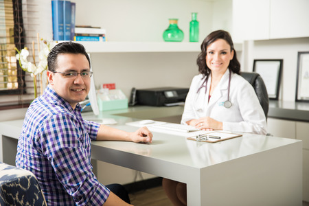 good looking: Good looking Hispanic patient visiting a doctor for a routine checkup in an office