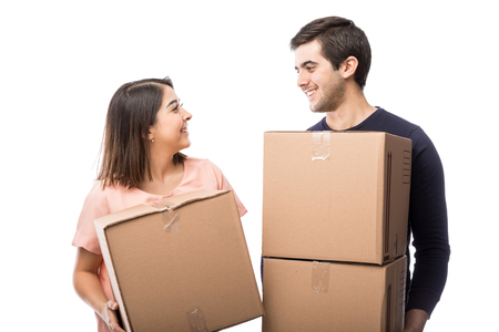 portait: Portait of an attractive young couple carrying some boxes to their new home and looking at each other Stock Photo