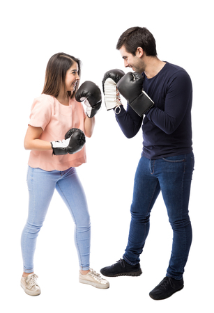 Attractive young couple wearing boxing gloves and having fun on a white background