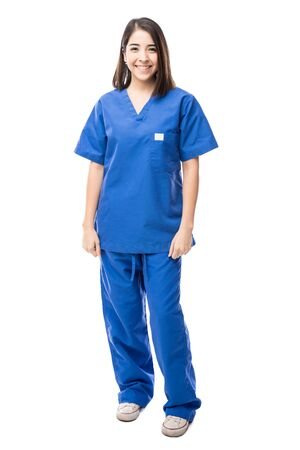 medical worker: Full length portrait of a beautiful young Hispanic nurse wearing scrubs in a white background
