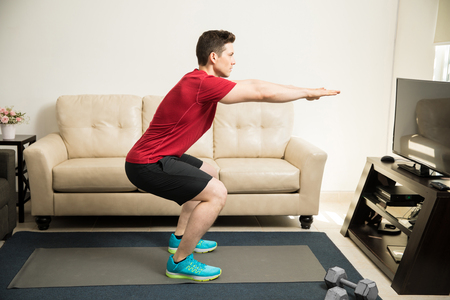 Profile view of an attractive young man doing squats and exercising at home 스톡 콘텐츠