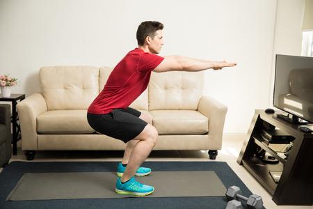 스쿼트를 하 고 집에서 운동하는 매력적인 젊은 남자의 프로필보기 스톡 콘텐츠