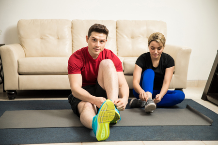 Attractive young couple tying their shoes and getting ready to exercise together at home