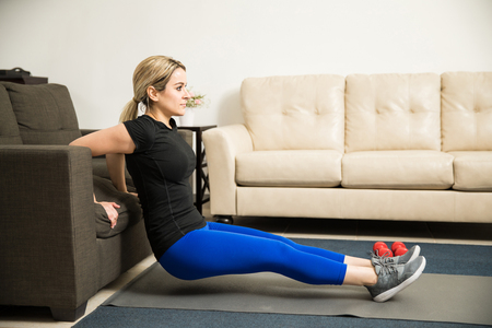 tricep: Profile view of a pretty young woman doing tricep dips leaning on a couch in her living room Stock Photo