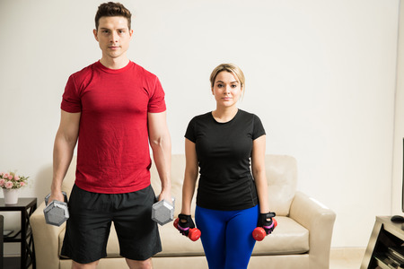 man working out: Portrait of a good looking young couple lifting weights and working out together at home Stock Photo