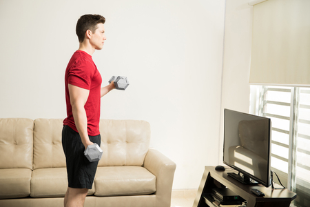 buen vivir: Profile view of a good looking strong man doing bicep curls in his living room