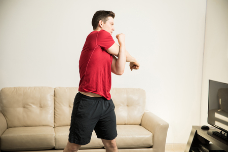 buen vivir: Good looking young man stretching his arms before working out in the living room