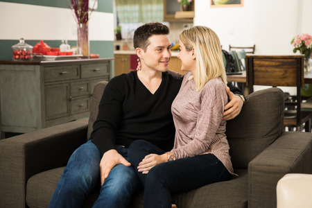 romantically: Attractive young Hispanic couple having a date at home and looking at each other romantically Stock Photo