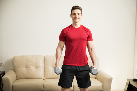 buen vivir: Portrait of a good looking strong Hispanic man holding a couple of dumbbells while working out in the living room