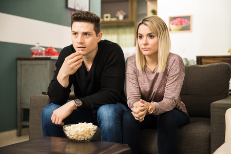 suspenso: Attractive young Latin couple in complete suspense while watching a movie and eating popcorn at home