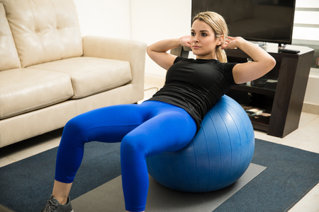 Portrait of a focused young woman leaning on a stability ball and doing crunches on her living room Stock Photo