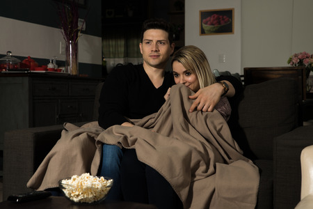 Portrait of an attractive young couple huddled together and under a blanket while watching a scary movie at night