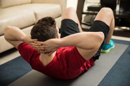 Rear view of a young athletic man doing crunches on an exercise mat at home Stock Photo