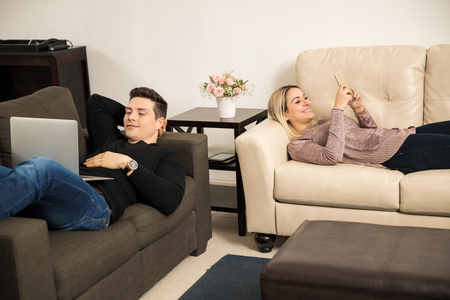 buen vivir: Good looking young couple laying on a separate couch in the living room and relaxing Foto de archivo
