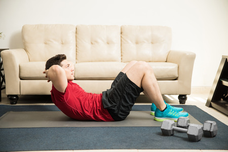 Profile view of a good looking athletic man doing crunches in the living room
