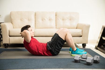 buen vivir: Vista de perfil de un hombre atlético guapo haciendo abdominales en la sala de estar