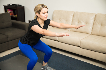 Cute young woman in sporty outfit doing some squats at home as part of her workout