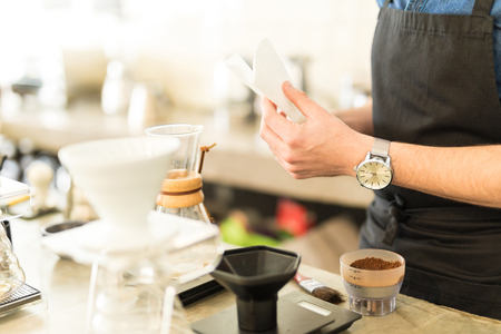straining: Young barista preparing and folding a coffee filter before brewing a cup of coffee in a cafe
