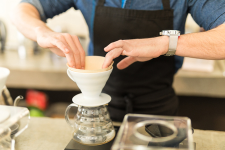straining: Closeup of a male barista placing a filter in a coffee brewer while making a cup of coffee in a cafe
