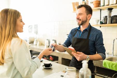 커피 숍에서 신용 카드로 그녀의 커피를 지불하는 젊은 여성의 프로필보기