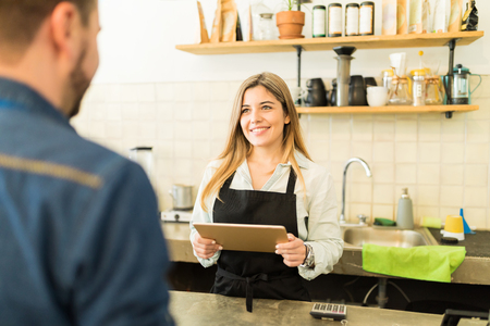hispanic woman: Portrait of a gorgeous female barista taking the order of a customer with a tablet computer and smiling