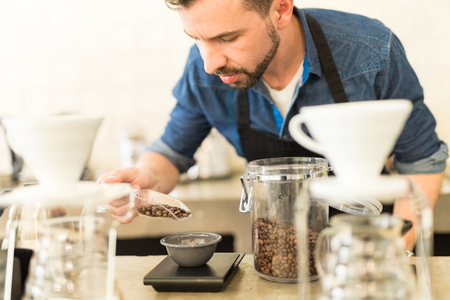 measuring cup: Handsome young barista carefully measuring coffee grains on a scale while preparing a cup of coffee