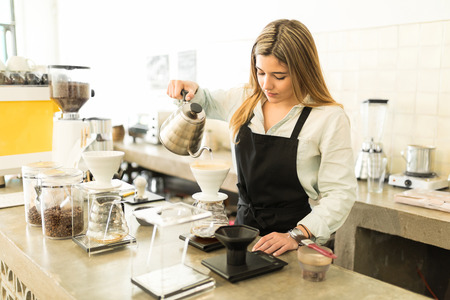 brewing: Portrait of a pretty female barista pouring water and brewing a cup of coffee at a coffee shop