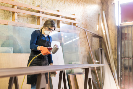 pulverizador: Attractive young woman painting a table with a spray gun while working in a woodshop