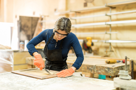 Portrait of an attractive young woman working as a carpenter in her woodshop using a gouge