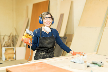 Portrait of a beautiful young Hispanic woman using a sander while working in a woodshop Stock Photo