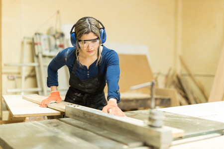 Portrait of a beautiful female carpenter using a table saw to cut some wood in a workshop