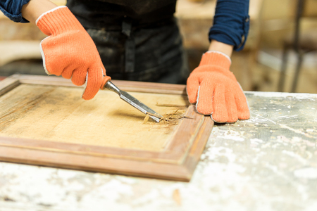 gouge: Closeup of a female carpenter doing some wood carving using a gouge in a workshop Stock Photo
