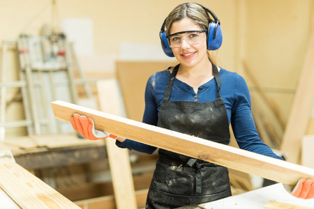 Cute young female carpenter cutting some wood in a table saw and enjoying her work Archivio Fotografico