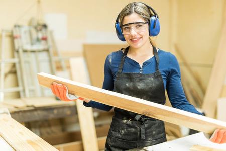 Leuke jonge vrouwelijke timmerman die wat hout in een lijstzaag snijdt en van haar werk geniet