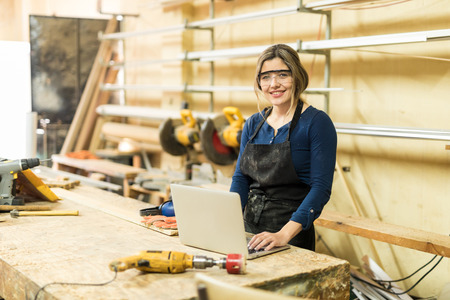 Portrait of a cute woman doing some work in a woodshop and using reviewing a design in a laptop Stock Photo