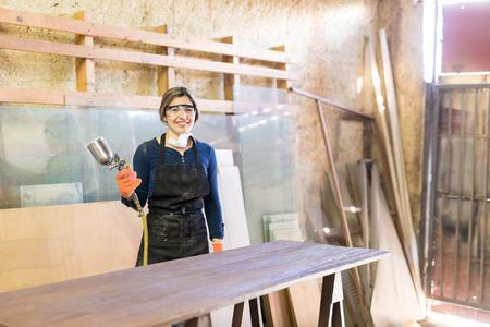 muebles de madera: Bastante joven carpintero de sexo femenino que pinta un vector con una pistola de pulverización y trabajar en un taller de carpintería