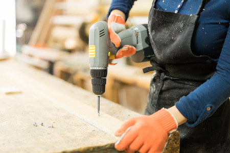 Closeup of a female carpenter using a screwdriver on a piece of wood in her woodshop