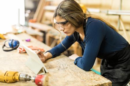 Close-up van een jonge vrouw die als timmerman werkt en een tabletcomputer in haar woodshop gebruikt