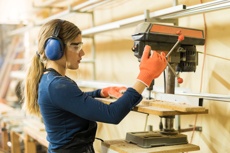 Profile view of a young female carpenter using a drill press on a wood board in a woodshop