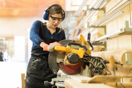 Attraktiver weiblicher Tischler, der einige Elektrowerkzeuge für ihre Arbeit in einem woodshop verwendet Standard-Bild
