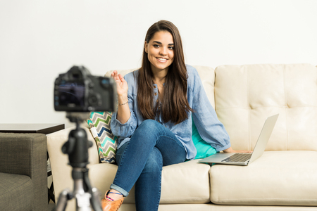Portrait of a cute young Hispanic woman recording a video blog from home and greeting her audience Stock Photo