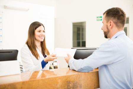 Réceptionniste attrayante donnant une enveloppe avec ses résultats de test à un patient en laboratoire