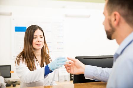 Attractive réceptionniste portant des gants et recevant un échantillon d'urine d'un patient dans un laboratoire Banque d'images - 74556662